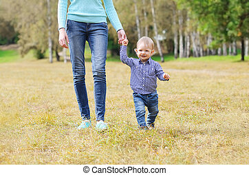 Happy mother and child walking together outdoors in park