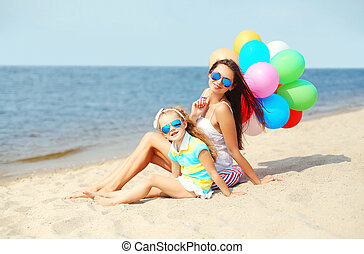 Happy mother and child with colorful balloons on beach near sea