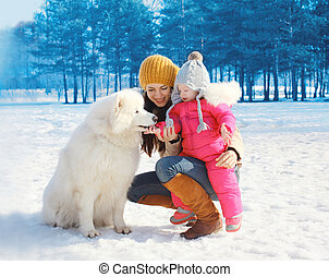 Happy mother and child with white Samoyed dog in winter day