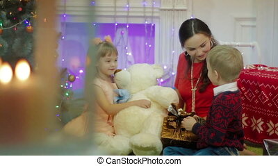 Happy Mother and Children with Christmas Gift near Christmas Tree at home
