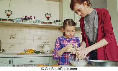 Happy mother and cute daughter cooking together and having fun stirring dough in hands. Family, food, home and people concept