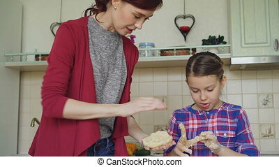 Happy mother and cute daughter cooking together and having fun stirring dough in hands in kitchen. Family, food, home and people concept