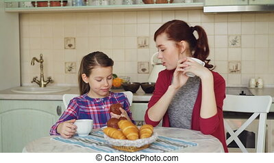 Happy mother and cute daughter having breakfast eating muffins and talking at home in modern kitchen. Family, food, home and people concept