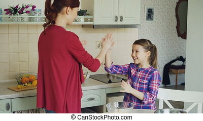 Happy mother and cute funny daughter playing clapping hands...