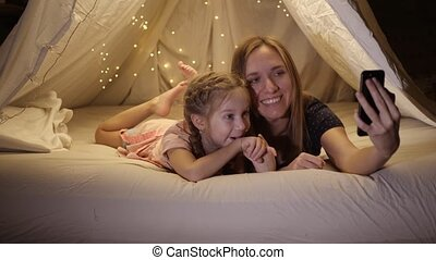 Happy mother and daughter are photographed on the phone in a makeshift tent in the living room, they smile and laugh