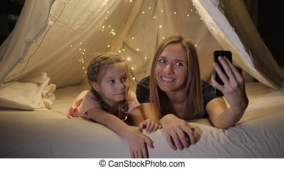 Happy mother and daughter are photographed on the phone in a makeshift tent in the living room, they smile