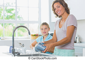 Happy mother and daughter doing the washing up together in...