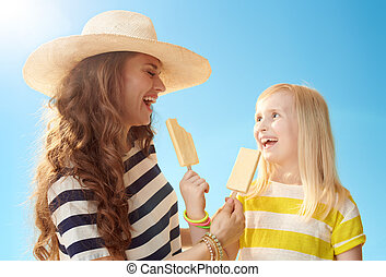 happy mother and daughter eating ice cream against blue sky
