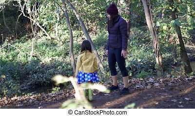 Cautious mother and happy little daughter in a forest kicking sticks and leaves into the river. Mother-daughter fun day in forest. Adventurous day in nature