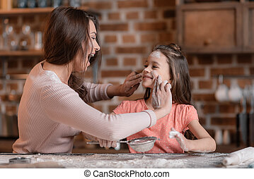 'Happy mother and daughter having fun while sifting flour at kitchen
