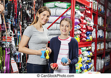 Happy Mother And Daughter Holding Toys In Pet Store