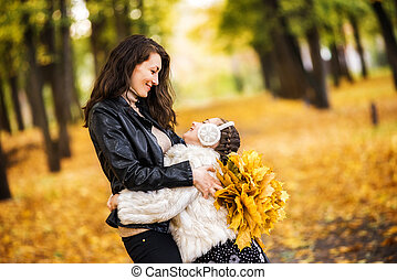 happy mother and daughter in the park in autumn