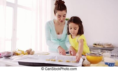 happy mother and daughter making cookies at home - family,...