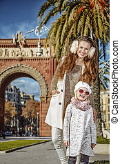 happy mother and daughter near Arc de Triomf in Barcelona, Spain
