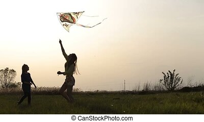 Happy mother and daughter on meadow with a kite