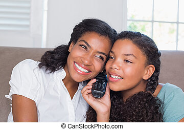Happy mother and daughter on the phone together on sofa at...