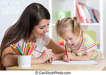 happy mother and daughter painting with pencils