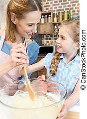 Happy mother and daughter preparing dough and looking at each other