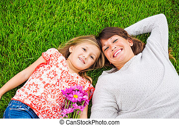 Happy mother and daughter relaxing outside on green grass. Spending quality time together, Real emotions
