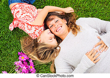Happy mother and daughter relaxing outside on green grass. ...