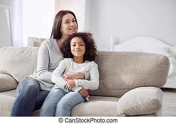 Happy mother and daughter siting on the couch