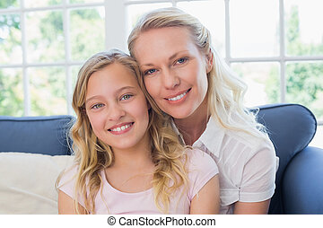 Happy mother and daughter sitting on sofa
