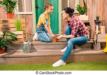 Happy mother and daughter sitting together on porch and cultivating plant