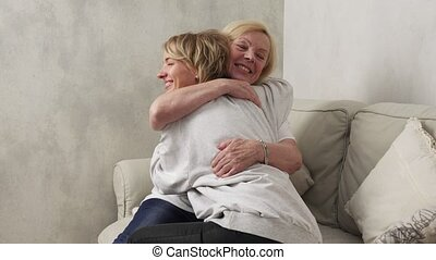 Happy mother and daughter - Happy elderly mother hugs and...