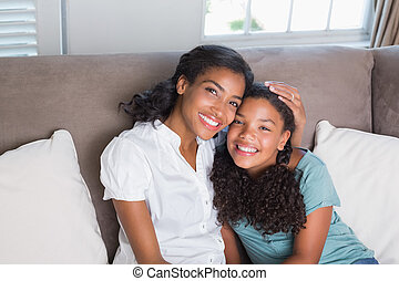 Happy mother and daughter together on sofa