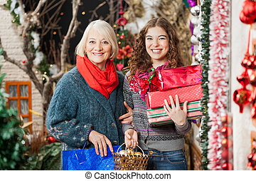 Happy Mother And Daughter With Christmas Presents In Store -...