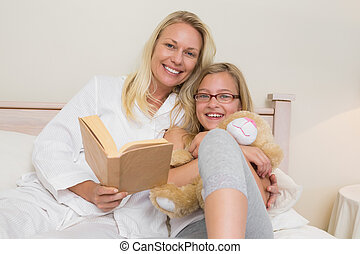 Happy mother and daughter with novel in bed