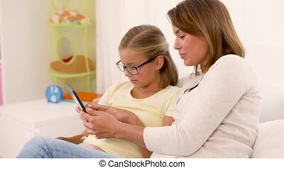 happy mother and daughter with tablet pc at home - people,...