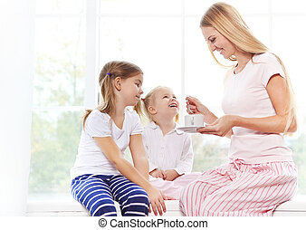Happy mother and daughters playing in the bedroom