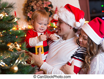 Happy mother and father with baby near Christmas tree