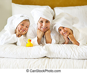 Happy mother and girls in bathrobes on bed - Happy mother...