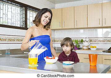 Happy Mother and her boy having breakfast