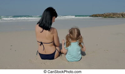 Happy mother and her charming little daughter are sitting on the beach by the sea