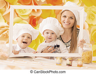 happy mother and her children in the form of chefs prepare a festive dinner