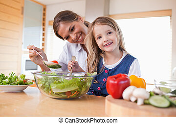 Happy mother and her daughter preparing a salad