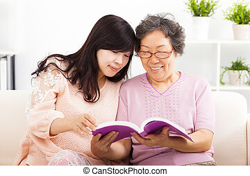 happy mother and her daughter reading book