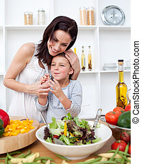 Happy mother and her daugther preparing a salad