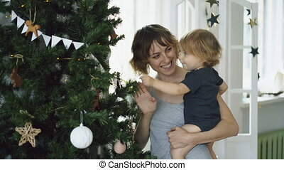 Happy mother and her little daughter playing near the Christmas tree at home