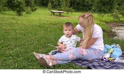 Happy mother and her little son enjoying playing on tablet...