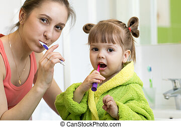 Happy mother and kid daughter brushing their teeth at home in the bathroom