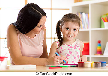 happy mother and kid daughter painting with pencils