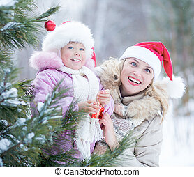 Happy mother and kid in Santa's hats with christmas tree decorations outdoor