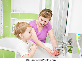 Happy mother and kid washing hands with soap together in bathroom