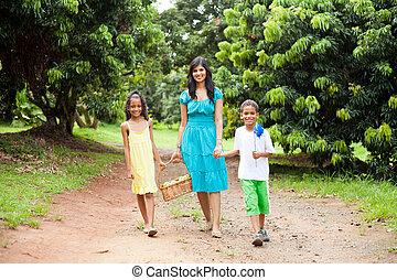 mother and kids walking in fruit garden
