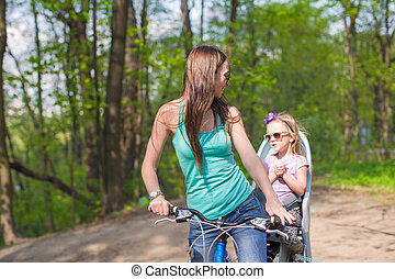 Happy mother and little daughter cycling bicycle at the park