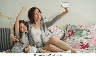 Happy mother and little girl taking selfie photo with...
